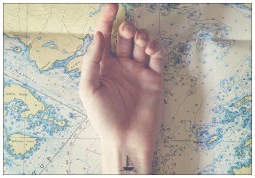 Рука с татуировкой корабликом.