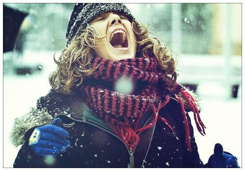 Девушка ловит снежинки.